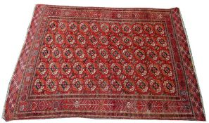 A Tekke Turkman carpet, the madder field with five columns of eleven guls, supporting medallions,