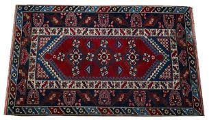 A Yagcibedir Turkish rug, the madder field with three flowerheads,