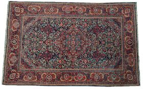A Kashan rug, Persian, the indigo field with a madder and pale indigo medallion, matching spandrels,