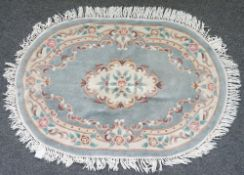 An oval hooked Chinese rug, sage floral field, 184cm x 123cm and a similar smaller, 150cm x 90cm.
