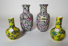 A pair of Chinese baluster vases, painted with flowers against a black ground, 17cm high,