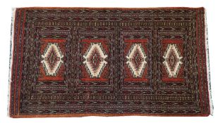 A Pakistan Bokhara rug, the brown field with four compartments, 167cm x 96cm.