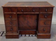 A George III mahogany kneehole writing desk with nine drawers about the knee on a plinth base,