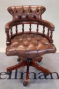 A modern stained beech office open armchair with brown leather buttonback upholstery,