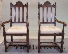 A pair of 18th century style oak high back open armchairs, 53cm wide x 116cm high.