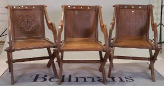 A group of three similar 20th century oak Glastonbury style chairs with solid backs and seats,