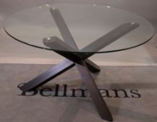 A glass circular dining table, on a stained beech 'X' frame base, 130cm diameter x 77cm high.