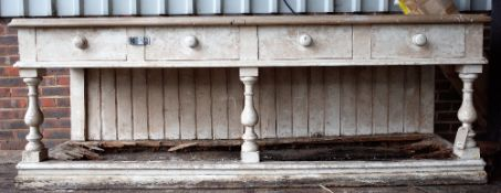 A early Victorian white painted pine dresser base with four frieze drawers on baluster supports and