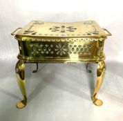 An early 19th century twin handled brass footman/trivet with pierced decoration and cabriole legs,