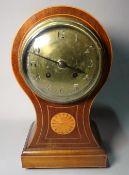 An Edwardian inlaid mahogany balloon shaped mantel clock with silver enamel dial,