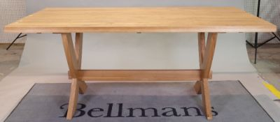 A modern oak rectangular dining table, on 'X' frame supports united by a stretcher,