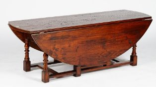 A 17th century style oak low gateleg table, with hinged oval top and two end drawers,