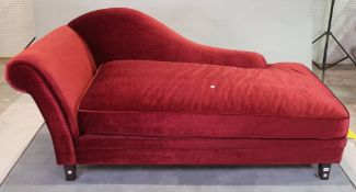 A modern hardwood framed chaise longue with red upholstery on tapering supports,