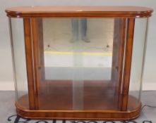 A modern fruitwood display cabinet with glass front and rounded ends, on plinth base,