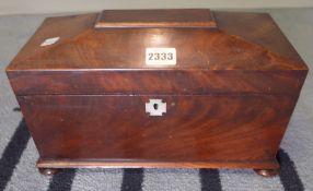A Regency mahogany tea caddy of sarcophagus form on bun feet, 31cm wide x 19cm high.