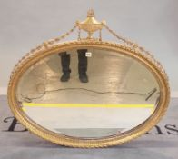 An Adams style giltwood oval wall mirror with urn and ribbon crest with bevelled glass,