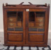 An Edwardian oak hanging wall cupboard with a central drawer flanked by two short drawers,