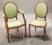 A set of nine Louis XVI style stained beech oval back dining chairs on fluted tapering supports,