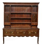 An 18th century inlaid oak dresser, the enclosed three tier plate rack with cupboards over...
