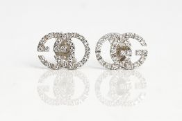 A Gucci pair of white gold and diamond earstuds, each designed as GG, mounted with circular...