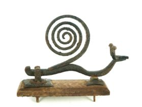 A novelty wrought iron door knocker in the form of a snail, on oak backing plate