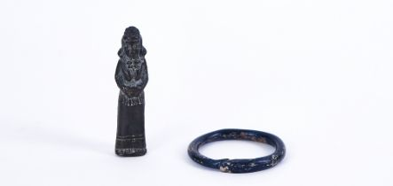 A ROMAN BLUE GLASS BANGLE AND A BRONZE AMULET, POSSIBLY INDIAN (2)