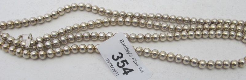 A white metal necklace consisting of a s