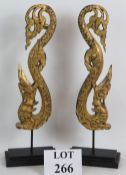 A decorative pair of Thai carved wooden naga or dragon finials with gilt finish and mounted on