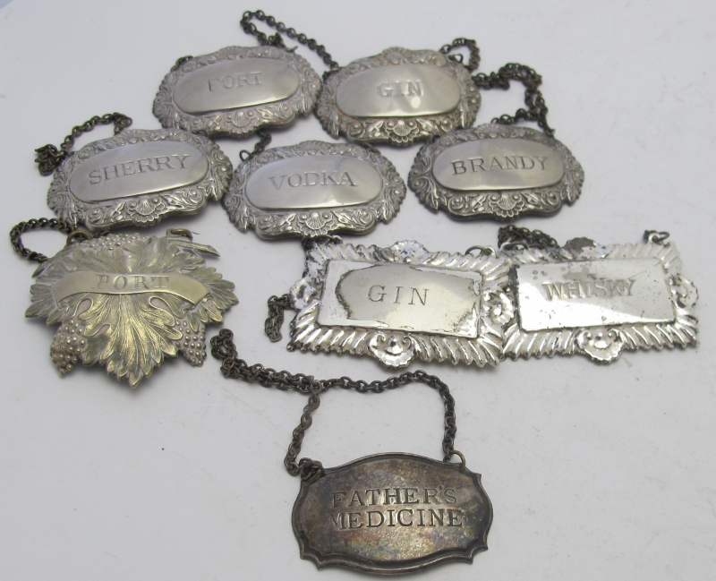 A collection of nine plated decanter labels to include a set of five 'Sherry', 'Port', 'Gin',