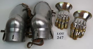 A pair of medieval style armoured gauntlets made of steel and brass and a similar pair of thigh leg
