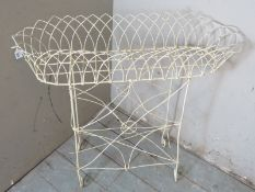 A vintage bent wire white metal trough planter on stand, raised on scroll feet.