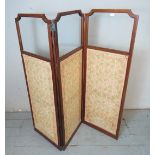 An Edwardian inlaid mahogany framed three section folding modesty screen featuring embroidered