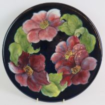 A Moorcroft pottery charger decorated with clematis pattern c1955, bearing incised and painted marks