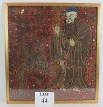 An antique Chinese silk panel with mirror and crewel work decoration depicting a monk and a
