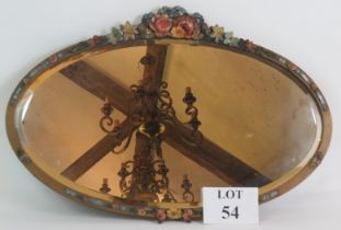 An oval early 20th Century Barbola mirror with floral moulding and bevelled glass. Width 60cm.