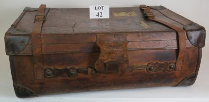 An antique leather travel trunk with wood slatted base and period labels. 82cm x 50cm x 30cm.