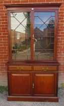 An Edwardian mahogany tall bookcase with dentil cornice over astral glazed doors opening onto