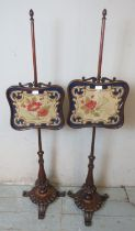 A pair of 19th century mahogany pole screens with tapestry panels raised on baluster turned pedestal
