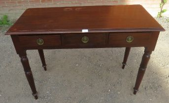 An Edwardian mahogany writing desk with three frieze drawers with brass drop ring handles, raised on