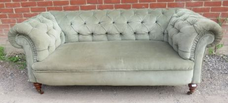 A Victorian two seat Chesterfield sofa upholstered in pistachio green velvet, raised on turned