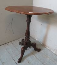 A Victorian mahogany wine table with a shaped top over a balluster column and scrolled tripod