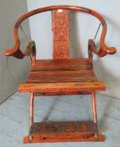 An early 20th century Chinese hardwood folding horseshoe chair, metal mounted and ornately carved