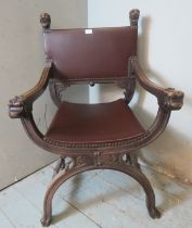 A vintage mahogany Savonarola chair ornately carved with grotesque mask finials & armrests, raised