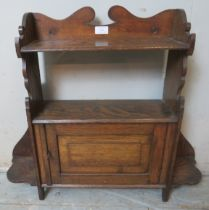 An Arts & Crafts wall hanging shelf with single cabinet. 60cm high x 70cm wide x 15cm deep (approx).