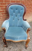 A Victorian mahogany spoon back show wood armchair upholstered in a buttoned blue velvet, raised