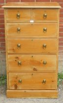 A tall pine chest of two over three long drawers with brass drop ring handles, raised on a plinth