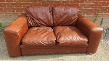 A contemporary two seater sofa upholstered in brown leather. 82cm high x 180cm wide x 102cm deep (