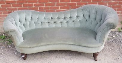 A Victorian sofa with ergonomically shaped backrests, upholstered in a green button velvet, raised