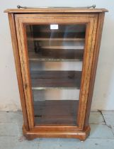 A Victorian walnut parquetry inlaid music cabinet with brass gallery rail and glazed door opening