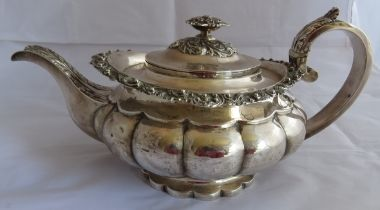 A decorative Georgian silver 2 pint teapot on circular scalloped base and have foliate and